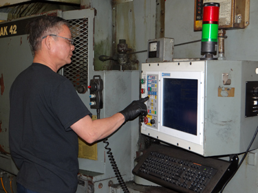 operator using Centroid M400 CNC control on a Blanchard CNC grinder